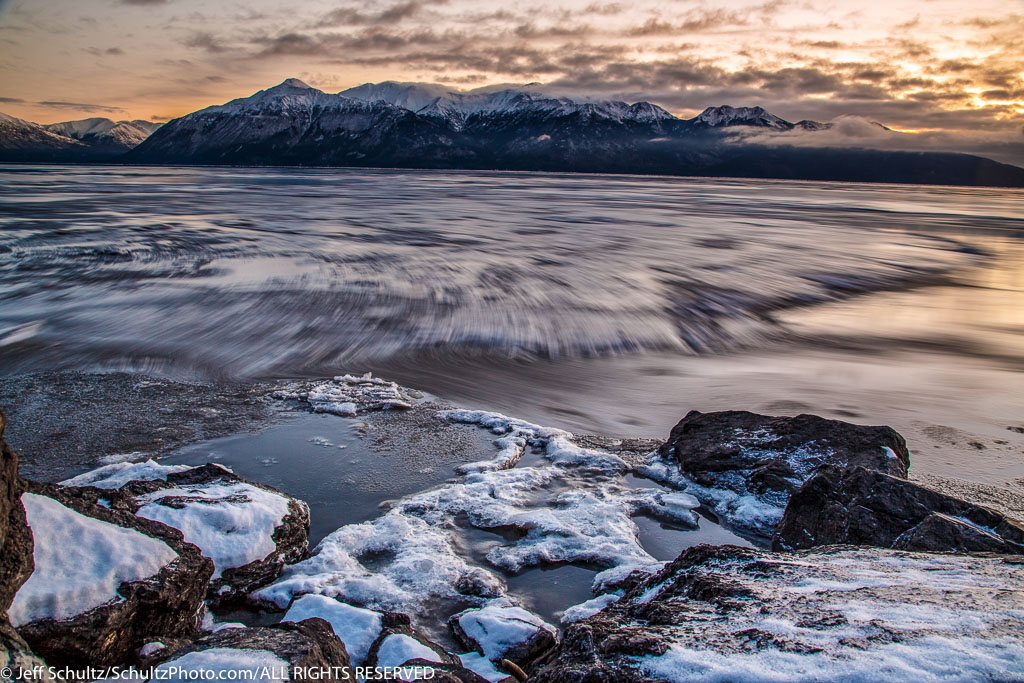 Winter landscape of cce sheets move along the outgoing tide of Turnagain Arm after sunset.  December, 2015