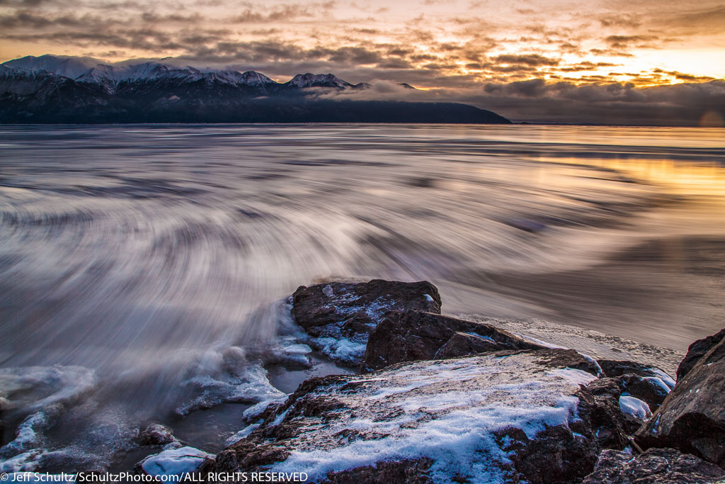 Winter landscape of ice sheets move along the outgoing tide of Turnagain Arm after sunset.  December, 2015