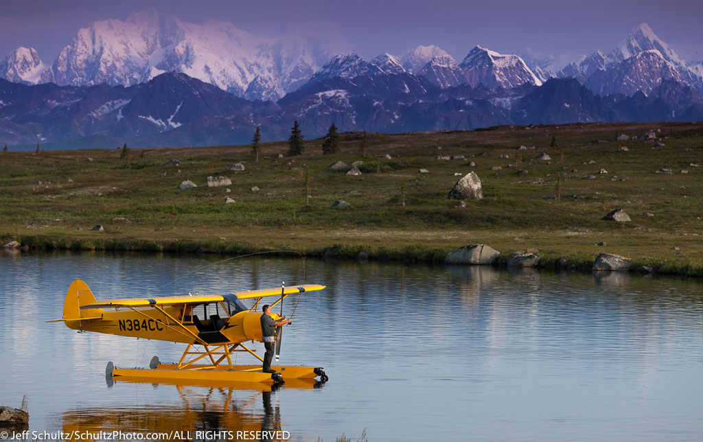 """A pilot fly fishes from his Super Cub floatplane on an unnamed lake in SouthCentral, Alaska with Alaska Range in the background, Summer"""